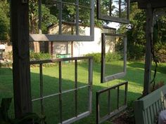 Several old window frames are strung together to make a divider for an outdoor patio space.