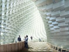 """More than 1,800 hollow rectangular fiberglass frames are stacked like space-age Lego blocks and appear to """"unzip,"""" curving outward from a straight line in the center to create an interior cavity that visitors can walk through or sit on."""