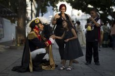 "Jesus Abreu (L), representing the South American independence leader Simon Bolivar for a play in the street, talks to a girl in Caracas"" - Bolivar everywhere 