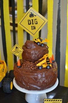 Cake was designed to resemble a muddy construction site with mini toy tractors and dump trucks and traffic cone shaped birthday candles