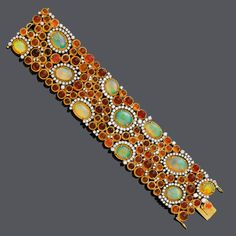 OPAL AND DIAMOND BRACELET. White and yellow gold 750. Set with 11 oval white opals within a diamond surround and numerous fire opal cabochons. Total weight of opals ca. 70.00 ct and diamonds ca. 8.80 ct. W ca. 3,8 cm, L ca. 18 cm.