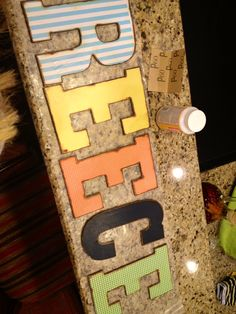 Wood letters from Michaels *(on sale for $1.50), stain edges, Mod Podge Scrap Book Paper on each letter, Distress ink on edges, modge podge two more coats and done!