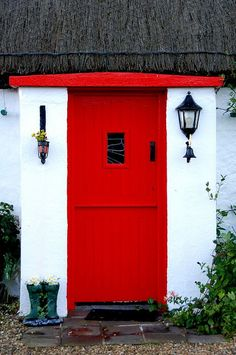 Red cottage door with thatched roof in Donegal, Ireland