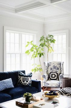 A traditional blue and white living room is brought to life with potted indoor houseplants and bold geometric ikat print pillows and a toile print arm chair.