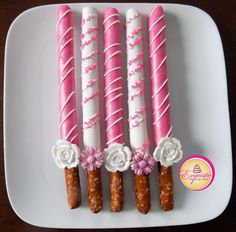 Tall pretzels rods dipped in pink and white chocolate, decorated with chocolate stripes, sugar crystals and edible sugar flowers