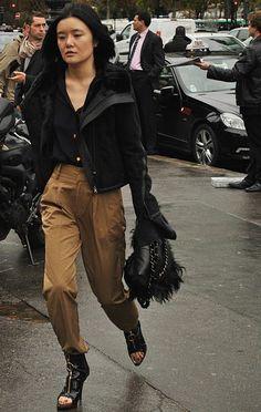 Outfit compuesto de chaqueta de aviador negra con pantalones color caramelo, blusa negra y botines y bolso a jeugo.