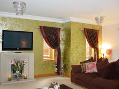 This photograph shows two single custom made slot top curtains, together with matching wallpaper and bespoke scatter cushions. The 'Hole in the Wall Curtains'professional fitters have draped each curtain by using holdbacks and tassel tiebacks.  Related posts:   Custom Made Slot Top And Voile Curtains….  Custom Made Shaped Pelmet With Curtains….  Custom Made Ribbon Tied Curtains With Roller Blind….