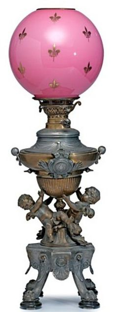 lighting, , A Victorian oil lamp, mixed metals having winged cherubs supporting a metal oil font, topped with a fuchsia glass globe having Fler-de-lis motif. Circa 1875-1900