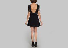 Robe patineuse noire, col bateau, manches mi longues en dentelle, dos nu boutonné au bas, taille ajustée, jupe à plis godets larges.  On aime cette robe Sessùn