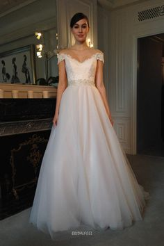 Ivory wedding dress features lace bodice and tulle skirt, applique off-the-shoulder cap sleeves with plunging V neckline, glittering beaded band at wiats, whilst sheer layered flowing long skirt.