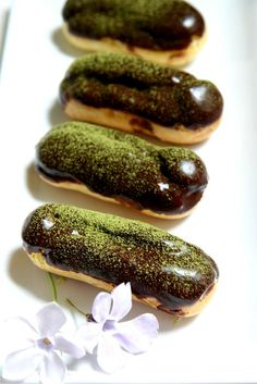 Chocolate glazed eclairs with ground pistachios sprinkled on top