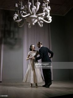 Fred Astaire and his sister Adele (aka Lady Cavendish, 1896 - 1981), dance under a white chandelier, 1947.