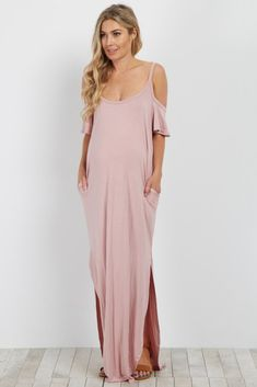 A solid cold shoulder maternity maxi dress. Rounded neckline. Slit along sides of dress. Front pockets. This style was created to be worn before, during, and after pregnancy.