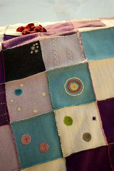 Felted wool quilt with bits of embroidery...lovely!