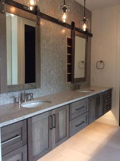 So much to love in this bathroom pic. The light fixture's simplicity adds to the clean sophisticated feel of the entire space. I love the mirrors on the barn door hardware concealing the medicine cabinets and the backsplash they carried all the way up. The lights under the vanity complete the look of the floating cabinetry. #bathroomgoals #barndoor