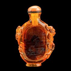 A Chinese amber snuff bottle  18th century  of flattened ovoid form, carved to depict a fisherman on a boat to front and nine calligraphic script to verso, mounted by twin chilong to sides.  H: 2 in., 5.1 cm