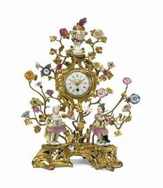 A LOUIS XV ORMOLU MEISSEN AND FRENCH PORCELAIN MANTEL CLOCK  CIRCA 1750  With figures of a putto disguised as a gallante and companion amid elaborate floral branches, the circular dial signed Le Roy à Paris, on a pierced base  13¼ in. (33.5 cm.) high