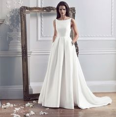 Caroline Castigliano HEPBURN bridal gown. Comprising a zibeline boat-neck and dropped back bodice, united with a cascading full pleated skirt and enchanting train.Zibeline boat-neck gown with full pleated skirt and concealed pockets Colour: Ivory Fabric: Mikado.