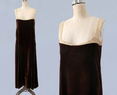 Unusual 1920s era house dress / gown in sumptuous chocolate brown liquid silk velvet. Gored design with flared, drapey skirt. Loose fit with no closures. Beautiful antique ecru lace yoke and straps. Even has little strings across the insides of the straps that snap into place over your bra/slip straps to hold them in place. Perfectly modern yet legitimately antique piece excellent for layering! Measurements: *no closures, slips over the head *meant to fit loosely. Recommended size M...