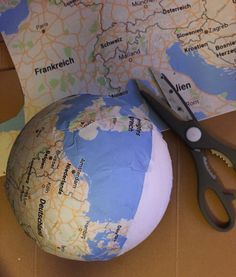 Reisegutschein basteln: Weltkugel aus Styropor mit Weltkarte bekleben und dekorieren.