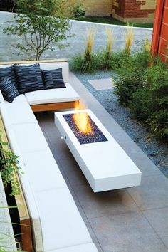 Decoration, Small Patio Design Plus L Shaped Outdoor Bench With Black Pillows Feat Ultra Modern Fireplace Idea And Greenery Planting ~ Fantastic Contemporary Fireplace Ideas for Comfortable Outdoor and Indoor Spaces #modernyardfireplaces