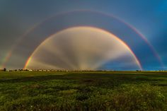 After a hard rain and a bit of hail,corpuscular rays appear to cast from the center of a double rainbow, near Reunion, Colorado.