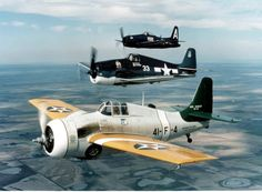 Three Grumman-designed fighters of the Confederate Air Force in flight (front to back): A General Motors FM-2 Wildcat (although painted as an F4F-3), a Grumman F6F-5 Hellcat, and a Grumman F8F-2 Bearcat.