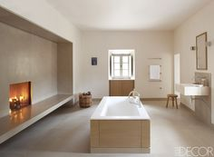 Paris-based interior designer Pierre Yovanovitch created a clean-lined master bathroom warmed by a fireplace when restoring his 17th-century château in Provence. The tub, positioned in the center of the room, is by Agape, and the fittings and towel rack are by Dornbracht. The floor is marble.    - ELLEDecor.com