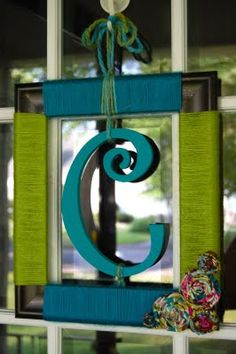 Summer wreath; picture frame wrapped with yarn with a painted wood letter hanging in the middle, cute, would be great for kids rooms too!