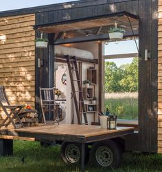 Tiny house with open window, lofted bed, and front porch.