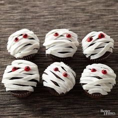 Start with frosted store-bought or homemade cupcakes for these quick and haunting Halloween cupcakes. To make the mummy cupcakes, follow these decorating steps: 1. Use a pastry bag with a basket-weave tip to pipe on white frosting. 2. Pipe on red frosting for the mummy's eyes. 3. Make two dots using black frosting for the pupils./