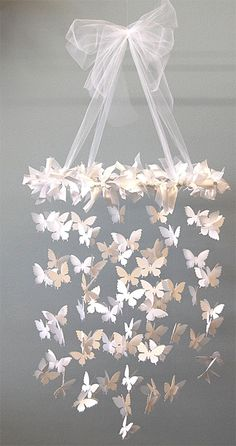 DIY decor - butterfly chandelier. Use coloured/patterned paper to tie in with your theme - looks effective with different shades of one colour; beige as an example in this pin