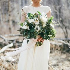 wedding bouquet with lots of green and ribbons to hold it together.
