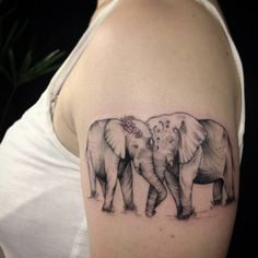 Upper arm tattoo of two elephants in love by Ivy Saruzi.