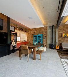 Decoração de casa de praia. Na sala de jantar, parede de tijolinhos, mesa de jantar retangular de madeira, cristaleira azul e pendente.