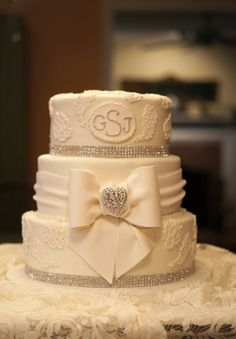 Fondant bow designed to highlight grandmother of the brides' antique brooch.  Design by Specialty Wedding Cakes by Heather LaPlante