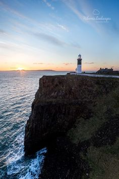 Sun rising over The Mull of Kintyre, Scotland, with the East Light on Rathlin Island, Co. Antrim, Ireland in the foreground.