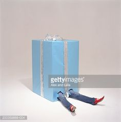 Stock Photo : Woman lying in large blue present with legs sticking out