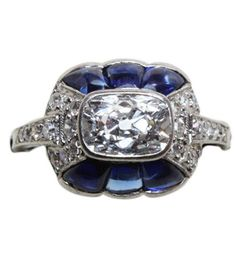 A platinum Art Deco ring with a cushion shaped diamond in its centre surrounded by brilliant cut diamonds on the sides and shoulders and six cut sapphires, signed and numbered: Linzeler  Marchak, 1421, Paris, ca. 1925.