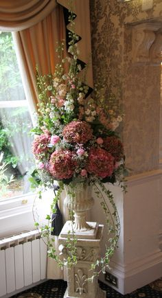 Beautiful Pink Caroline Delphiniums, Antirhinnums and Stocks with some late Peonies and Classic Hydrangeas, Eucalyptus and trails of variegated Ivy created voluptuous pedestal design