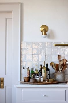 Brass accents lend warmth throughout the house. Here, the utensil bar is paired with Uptown Brass Sconces, $385, from Jones County Road.Photograph by Jersey Ice Cream Co.