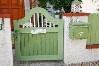 Grün lackiertes Holz Gartentürchen mit Namensschild, neben Mauerstück mit aufgehängtem Briefkasten in gleicher Farbe