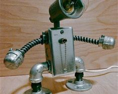 "Handmade ""industrial robot"" lamp design with functioning light and pull chain style switch. This lamp is hand made in my Brooklyn studio. (and is awesome! Wall E, Industrial Robots, Industrial Style, Fixer Upper Decor, Pull Chain, Pipe Lamp, Lamp Design, Cool Things To Make, Door Handles"