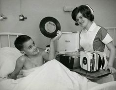 1960s, A friendly Candy Striper offering a record player and 45s.