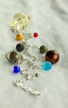 Solar System Bracelet gift is perfect for teachers or anyone! Made and sold by a 7 year old boy! He uses semi precious stone and glass beads. Crystal Jewelry, Jewelry Necklaces, Bracelets, Jewellery, Solar System Bracelet, Bff, Sand Dollar Necklace, Ocean Jewelry, Galaxy Jewelry