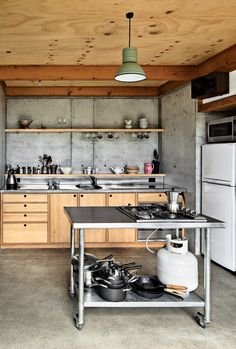 """The designers fabricated everything in the house, down to the quarter-sawn pine and macrocarpa-wood kitchen cabinetry and concrete floor. """"Physically the most challenging part of the build was wrestling an incredibly slippery concrete pump up the muddy driveway in the rain!"""" says designer Ben Mitchell-Anyon. The enamel pendant light is vintage. Photo by: Paul McCredie"""