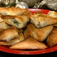 [MICHAEL SYMON'S SPINACH PHYLLO PIES] EVOO, onion, garlic, toasted pine nuts, chili flakes, dill, salt, cooked spinach, feta, lemon zest, Phyllo dough & butter.