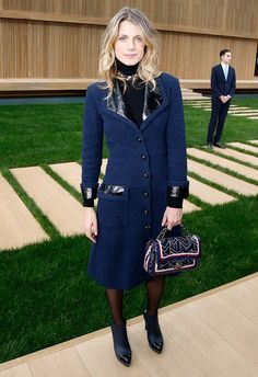 Melanie Laurent wears a black turtleneck, navy blue coat dress, graphic-print Chanel bag, tights, and cap-toe boots