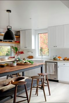 dark butcher block island, white oak floors, retro pendants, white cabinets, wood hand crafted stools