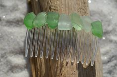Lovely green, and frosted green sea glass hair comb. The colorful frosted beach glass adorns an acrylic hair comb. The hair comb is perfect for a beach wedding or just frolicking in the surf while enjoying a day at the beach. The hair comb is handmade. Each piece of sea glass was carefully selected for its unique and compelling ocean shades, combined they create a lovely hair comb.  The sea glass is genuine and was collected on the rocky shores and sandy beaches of Casco Bay, Maine. The sea…